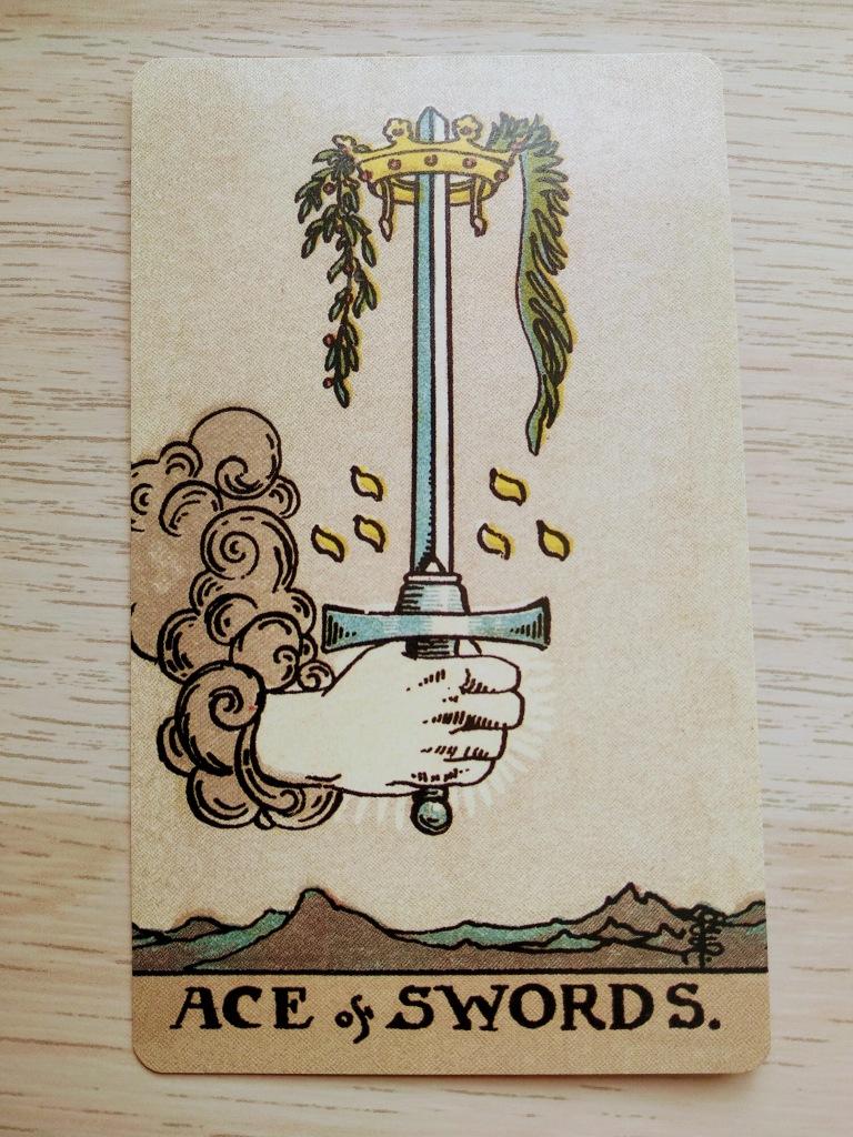 En el cielo, una mano sostiene una espada por el pomo, con la punta hacia arriba. La mano sale de una nube de tormenta. En la punta de la espada hay una corona con dos ramas de plantas verdes. En el suelo vemos un paisaje montañoso árido.
