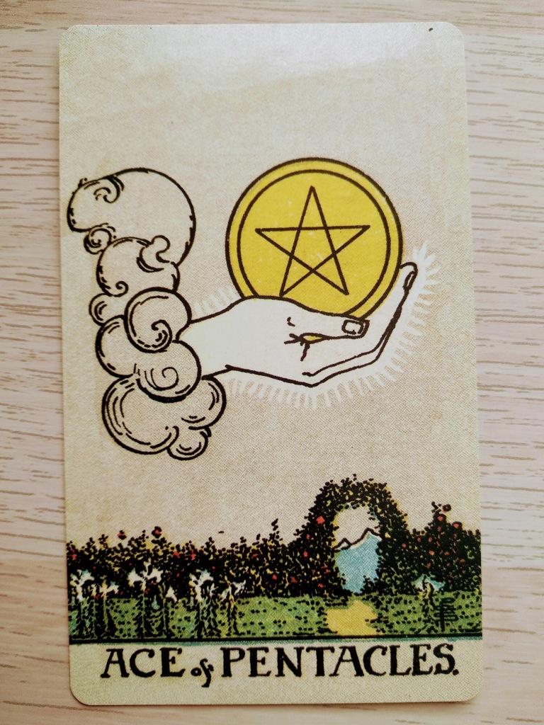 En la imagen hay una carta. Una mano en el cielo tiene un pentáculo (una moneda de oro con una estrella de cinco puntas grabada) en modo de ofrenda. En el suelo hay un jardín con una puerta que lleva a la montaña.